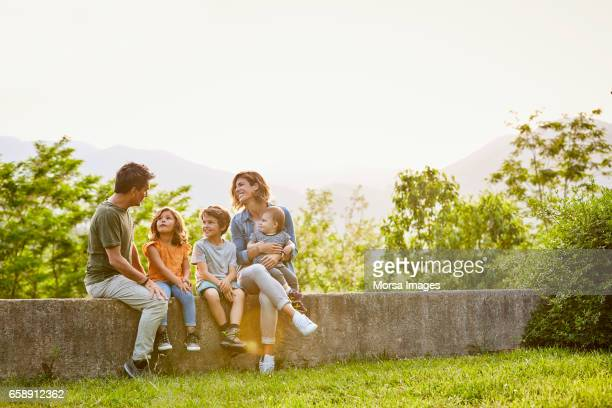 smiling mother and children listening to father - mom sits on sons lap stock pictures, royalty-free photos & images