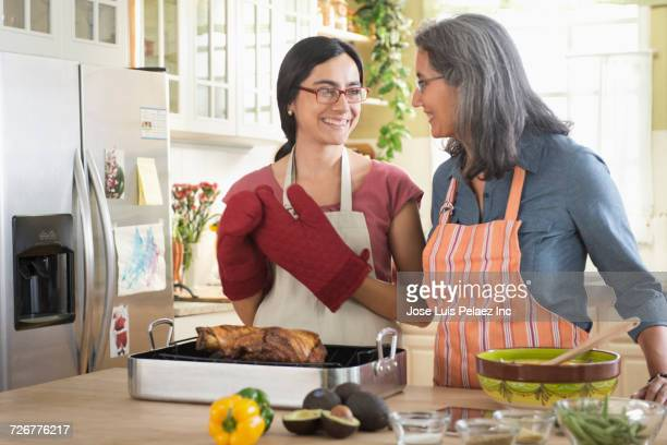 Smiling mother and daughter cooking in domestic kitchen