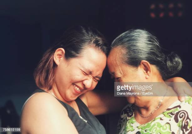 smiling mother and daughter embracing - somente adultos - fotografias e filmes do acervo