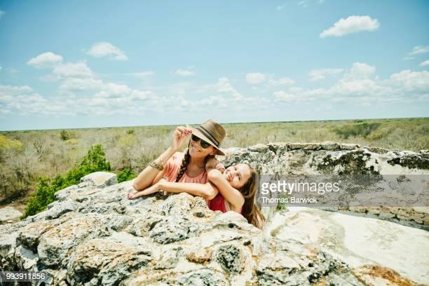 Smiling mother and daughter hanging out at top of Mayan pyramid while exploring Mayapan ruins