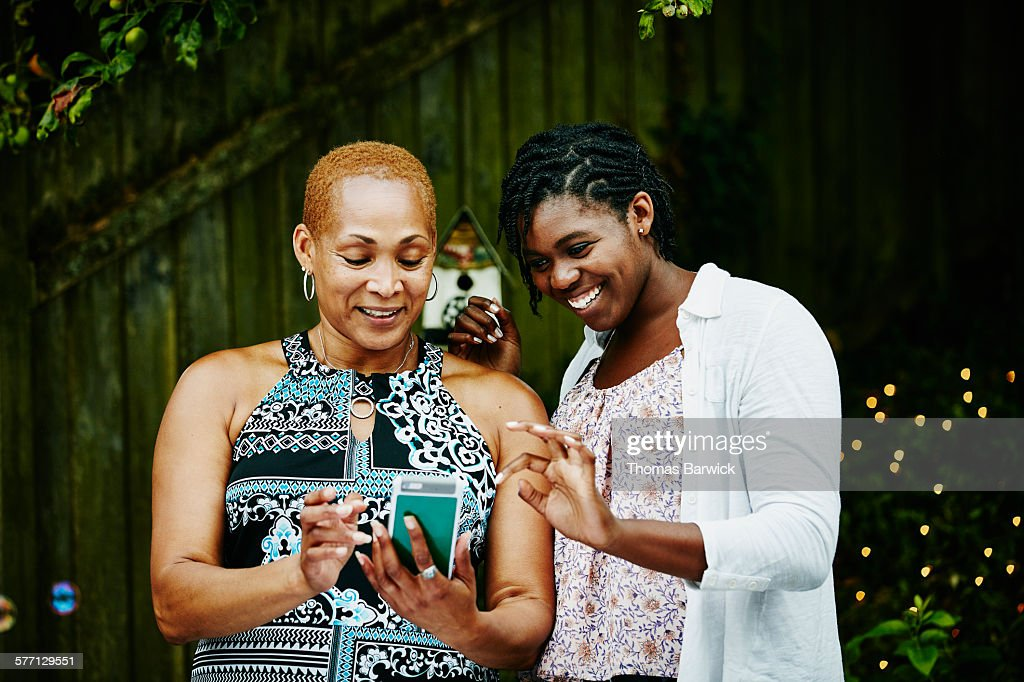 Smiling mother and daughter looking at smartphone : Stock Photo