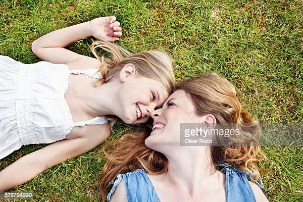 Smiling mother and daughter (7-9) lying on grass