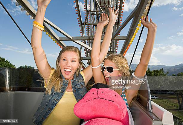 Smiling mother and daughter on ferris wheel