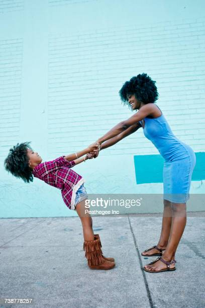 Smiling mother and daughter playing on sidewalk