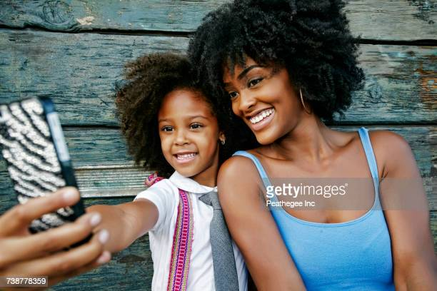 Smiling mother and daughter posing for cell phone selfie