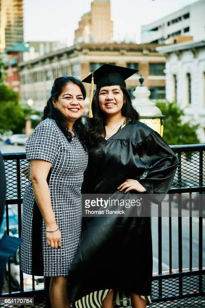 Smiling mother and daughter posing for graduation photos during celebration on restaurant deck