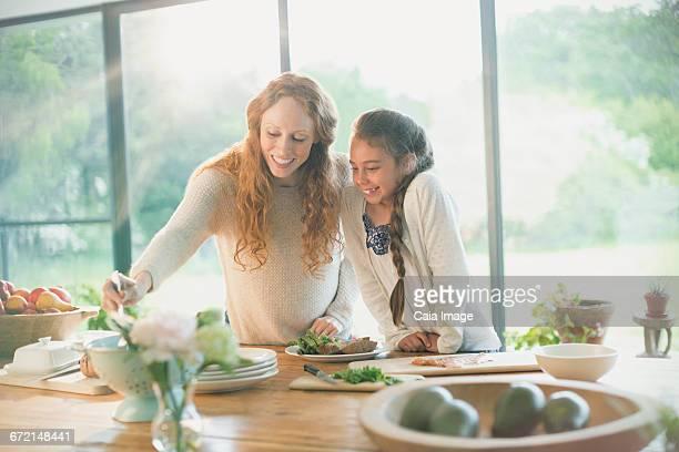 Smiling mother and daughter preparing food