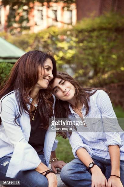 smiling mother and daughter resting at park - capelli castani foto e immagini stock