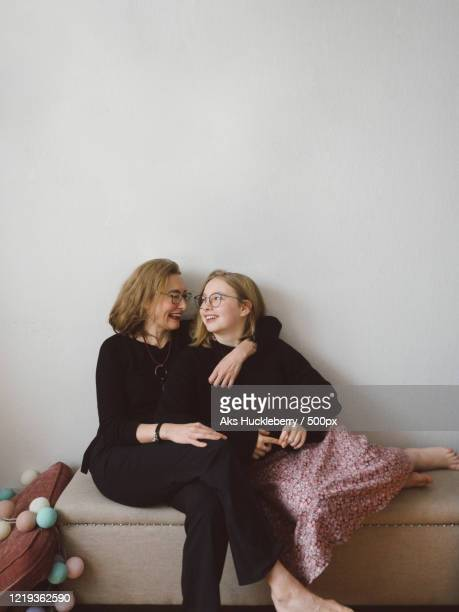 smiling mother and daughter sitting together and embracing - showus stock-fotos und bilder
