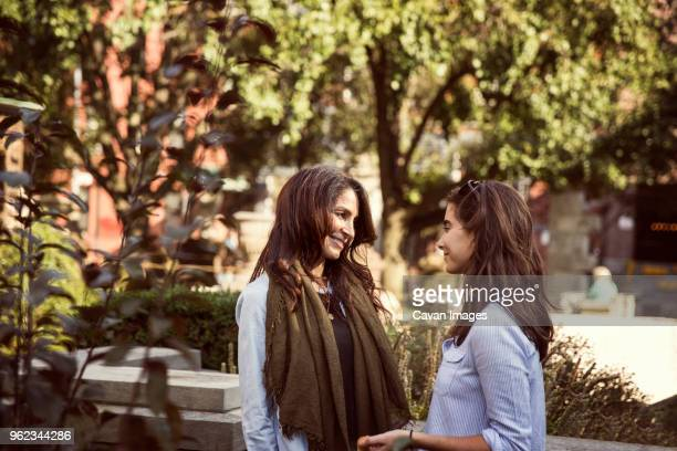 smiling mother and daughter talking while standing by plants - capelli castani foto e immagini stock