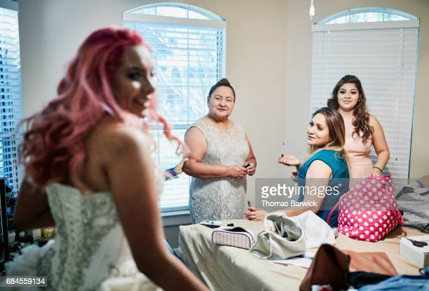 Smiling mother and grandmother looking at granddaughter dressed in quinceanera gown