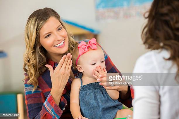 Smiling mother and her cute toddler daughter practicing sign language