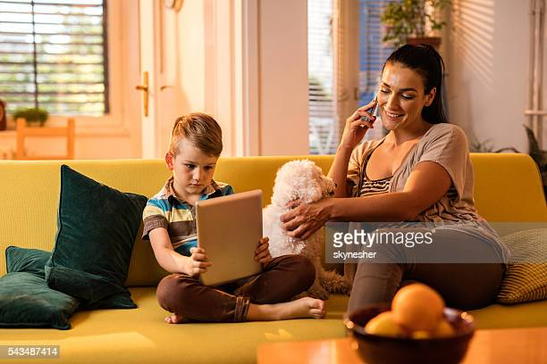 Smiling mother and her son using wireless technology at home.