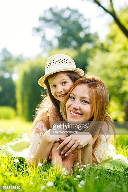 Smiling mother and little girl enjoying lying down on grass.
