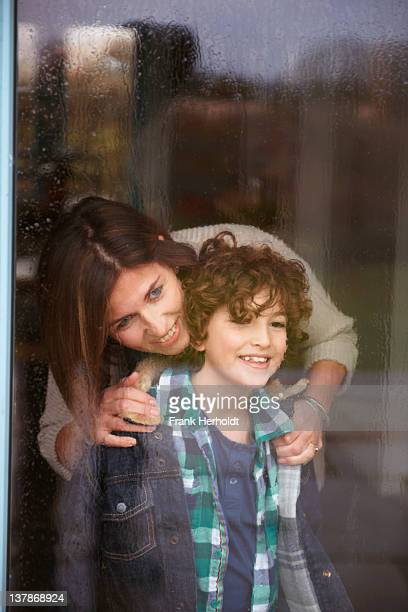 smiling mother and son looking out rainy window - mother son shower stock photos and pictures