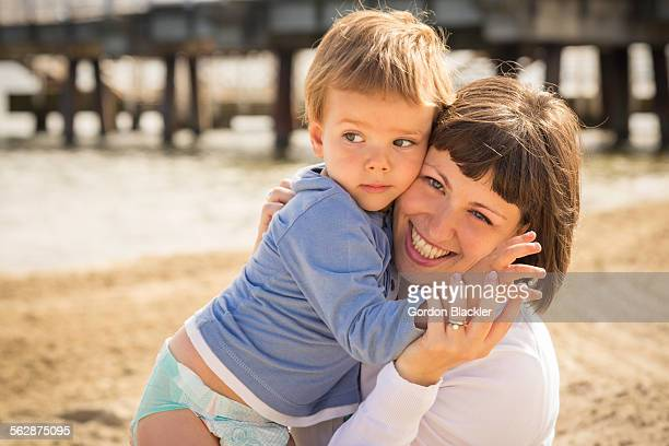 Smiling mother and toddler son embracing on beach near long pier. Gdansk, Poland