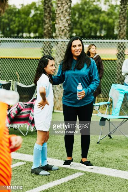 Smiling mother and young female soccer player in discussion on sidelines after game