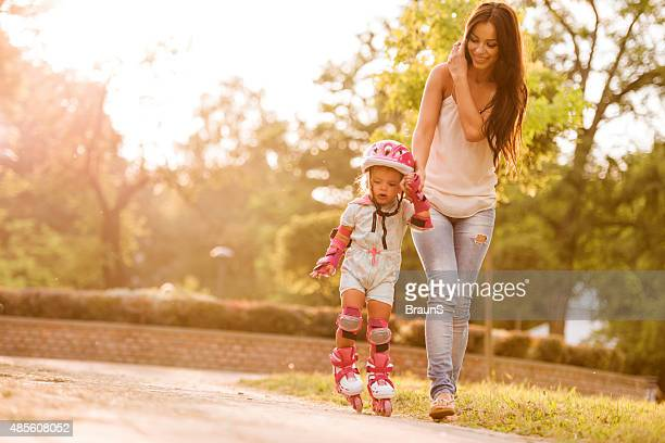 Smiling mother assisting her little girl in rollerblading.