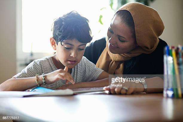 Smiling mother assisting son in using digital tablet while studying at home