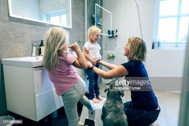 smiling mother bonding while kneeling in bathroom by dog at home - one animal stock pictures, royalty-free photos & images