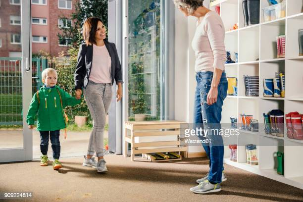 Smiling mother bringing boy to kindergarten
