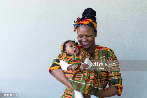 smiling mother carrying cute daughter against wall - tradition stock pictures, royalty-free photos & images