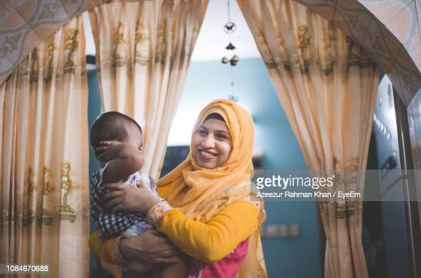 smiling mother carrying son at home - bangladesh mother stock pictures, royalty-free photos & images