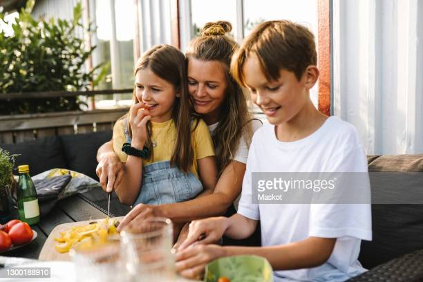smiling mother cutting vegetable on table in balcony - bruder stock-fotos und bilder