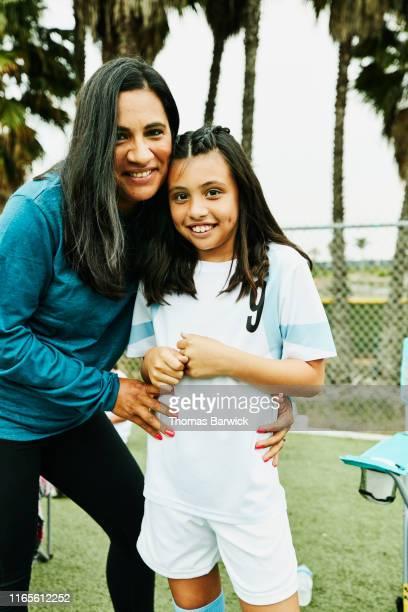smiling mother embracing daughter on sidelines after soccer game - fußballtrikot stock-fotos und bilder