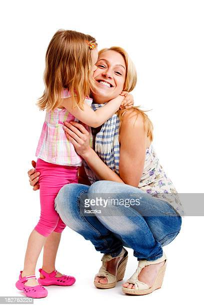 Smiling mother embracing young daughter on white background