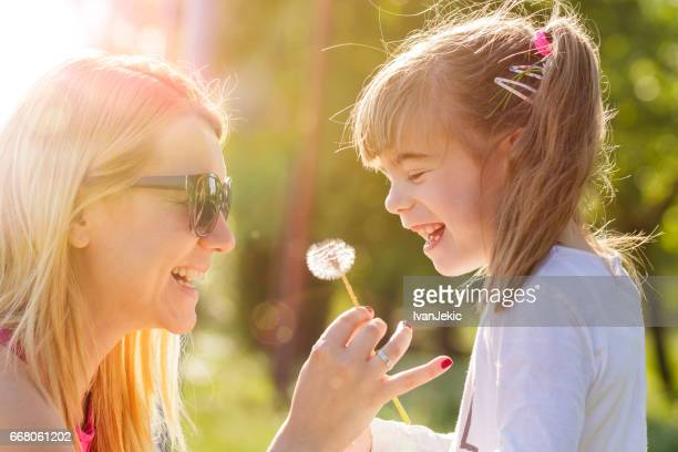 Smiling mother giving a flower to her daughter