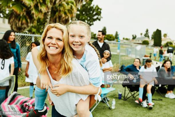 smiling mother giving daughter piggy back ride on sidelines after soccer game - community stock pictures, royalty-free photos & images