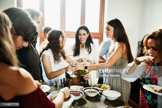 Smiling mother hanging out with daughters in kitchen during family dinner party