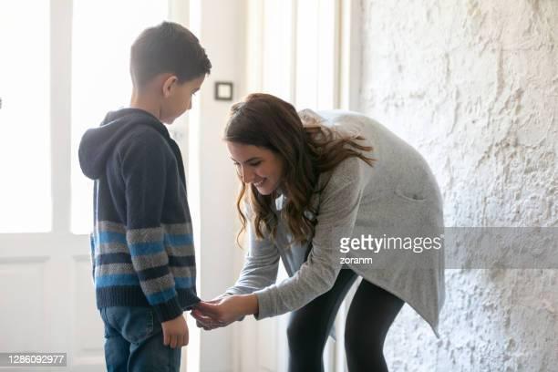 mère de sourire aidant son fils avec la fermeture éclair de veste - manteau et veste photos et images de collection