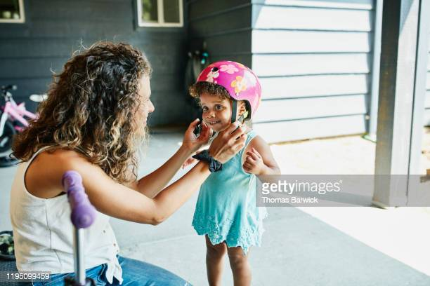 smiling mother helping toddler daughter buckle helmet before riding scooter - family stock pictures, royalty-free photos & images