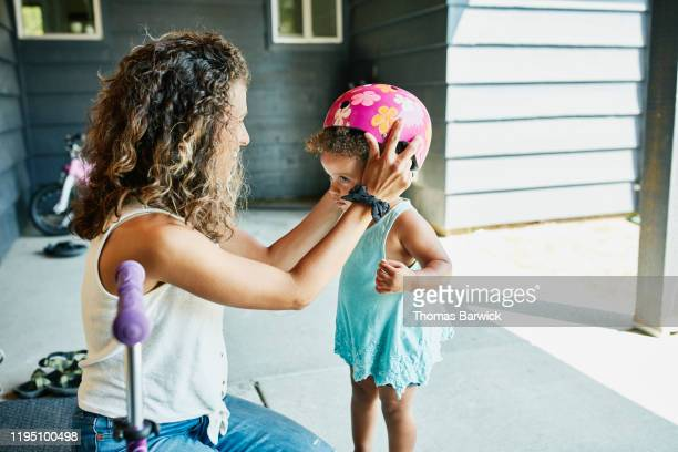 smiling mother helping toddler daughter put on helmet before riding scooter - protection stock pictures, royalty-free photos & images