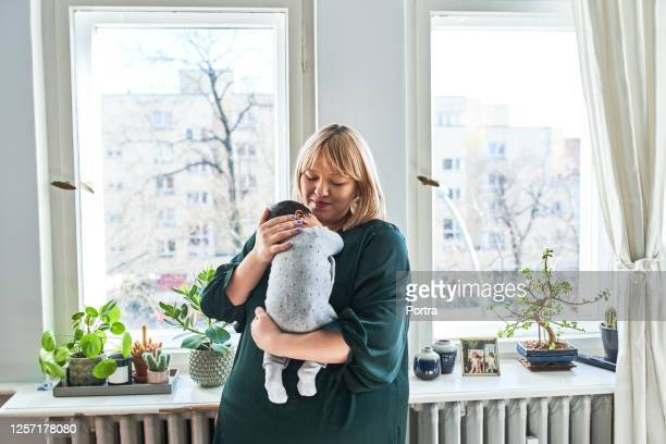 smiling mother holding baby at home - newborn stock pictures, royalty-free photos & images