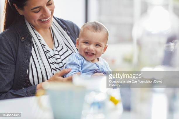 Smiling mother holding baby boy in kitchen