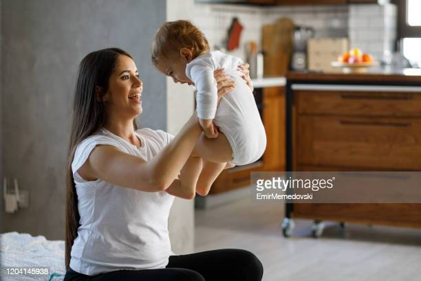 smiling mother holding her baby boy - emir memedovski stock pictures, royalty-free photos & images
