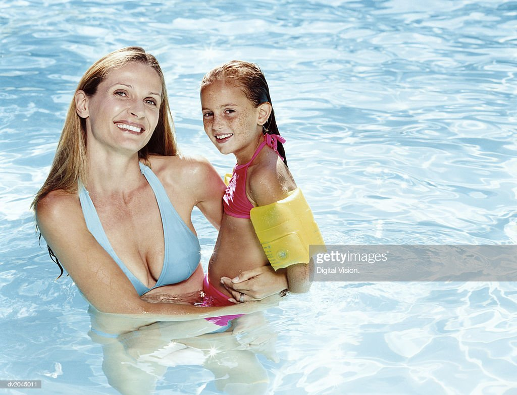Smiling Mother Holding Her Daughter in a Swimming Pool : Stock Photo