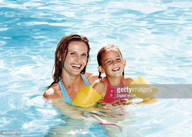 Smiling Mother Holding Her Daughter in a Swimming Pool