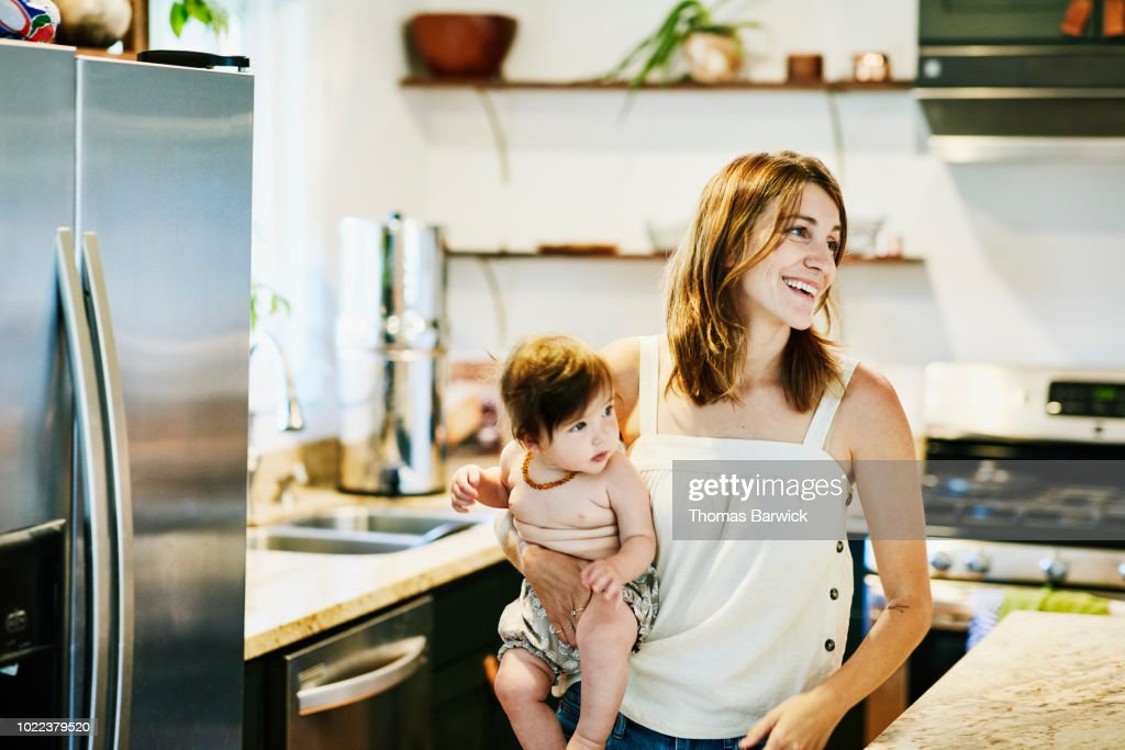 Smiling mother holding infant daughter in home kitchen : Stockfoto