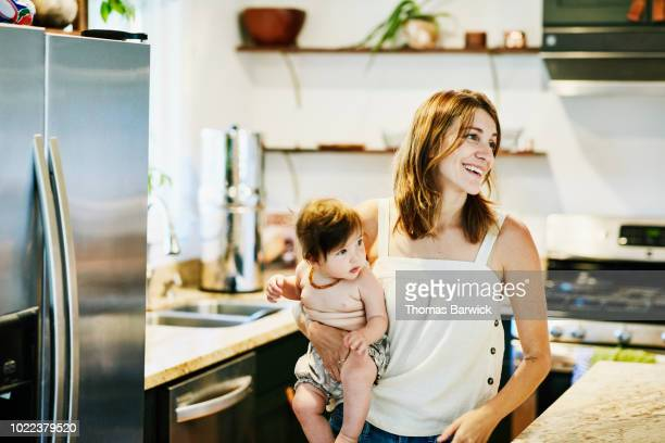 smiling mother holding infant daughter in home kitchen - ungestellt stock-fotos und bilder
