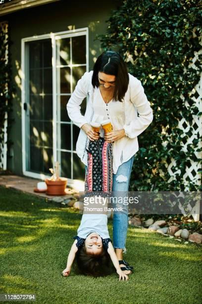 smiling mother holding laughing young daughter upside down in backyard - família de um filho - fotografias e filmes do acervo
