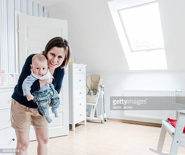 Smiling mother holding little baby boy on hands, baby's room