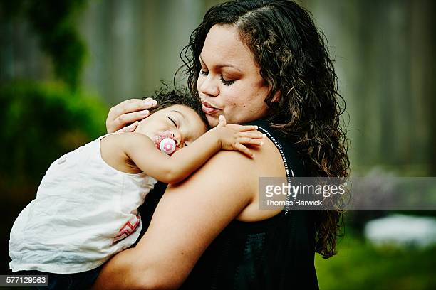 Smiling mother holding sleeping toddler daughter