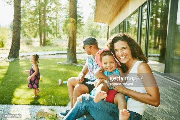 smiling mother holding toddler daughter in lap while sitting on front porch of vacation home - family stock pictures, royalty-free photos & images