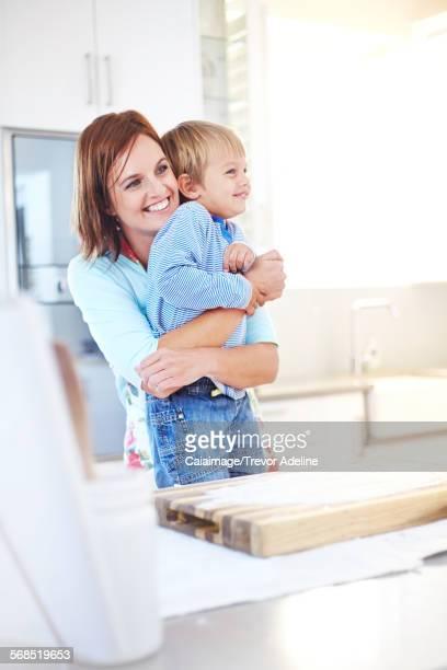 Smiling mother hugging son in kitchen