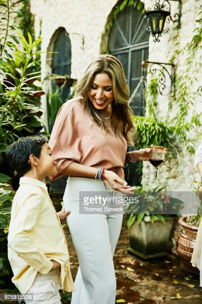 Smiling mother in discussion with laughing son during party in backyard garden