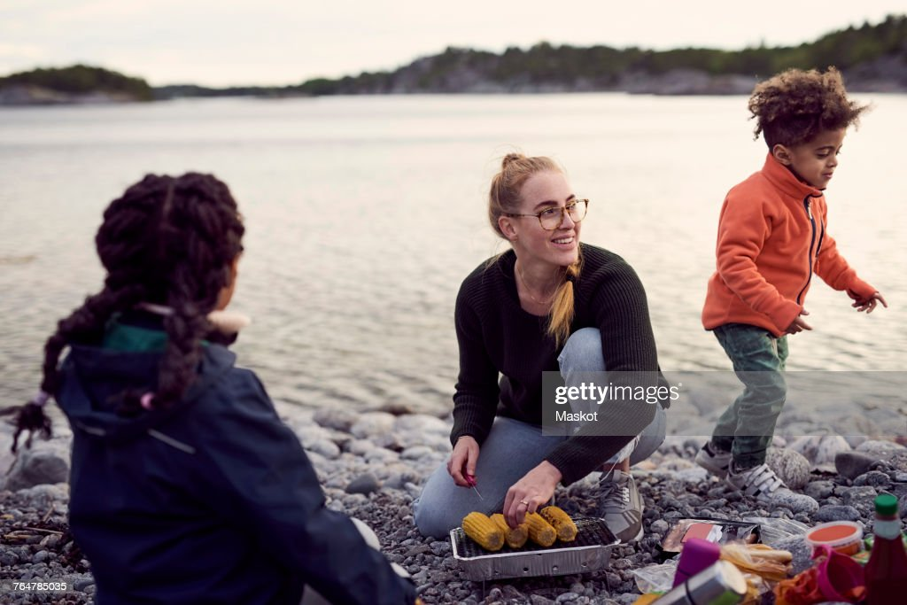 Smiling mother kneeling while cooking corns on barbecue grill amidst children at beach : Stock Photo